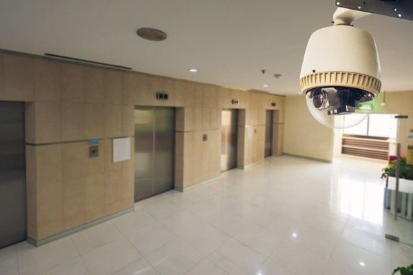 surveillance camera monitoring private hallway with 2 elevators