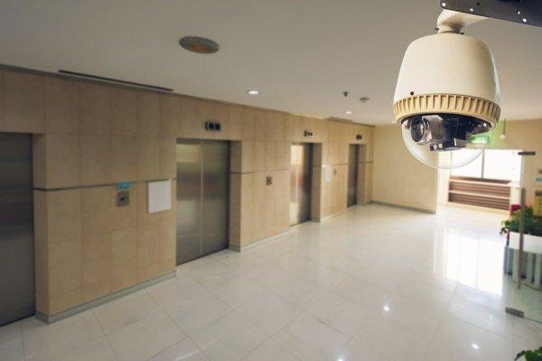 surveillance camera monitoring private hallway with 2 elevators